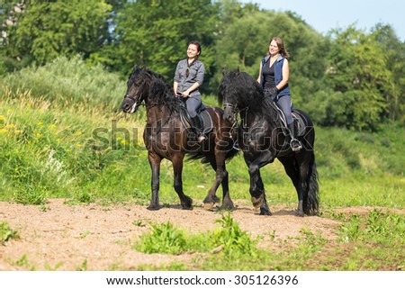 Two beautiful young women riding horses at the river shoe. - stock photo