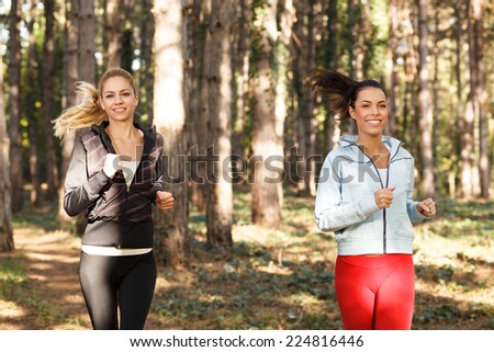 Two beautiful young women  running through the park - stock photo