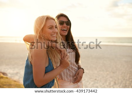 Two beautiful young women strolling on a beach. Female friends walking on the beach and laughing on a summer day, enjoying summer vacation. - stock photo