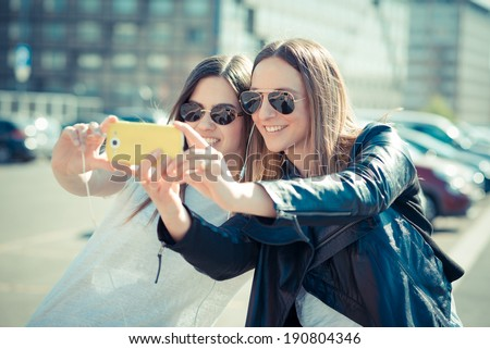 two beautiful young women using smart phone for selfie in the city - stock photo