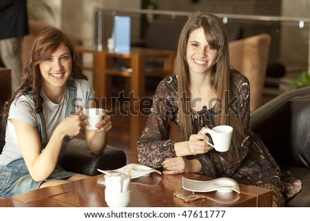 Two beautiful young women with great teeth enjoying their lunch break, drinking coffee, smiling to the camera - stock photo