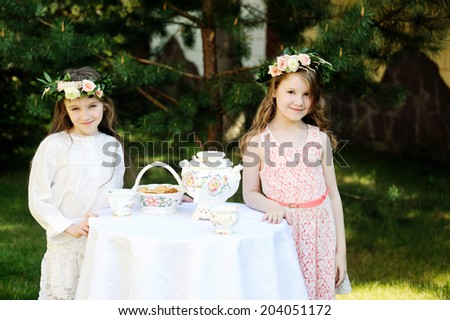 Two beauty kid flower girls near the tea table outdoor - stock photo