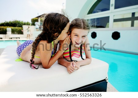 Two beauty kid girls having fun outdoor near the pool in warm summer day