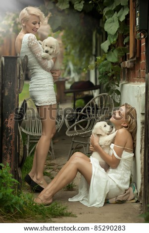 Two beauty ladies holding cute puppies - stock photo