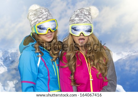 Two beauty smiling women in winter in mountains - stock photo
