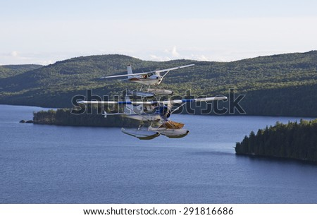 two beaver airplanes flying side to side over a wild lake - stock photo
