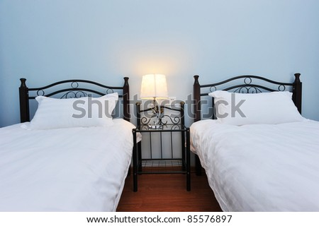 Two beds bedroom with bedside table and lamp. - stock photo
