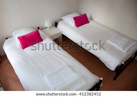 Two beds with bedside table and white lamp. - stock photo