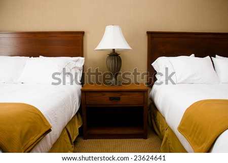 Two beds with white sheets and a mustard bed skirt on either side of a lamp and white lampshade on top of a wood bedside table in a hotel room. - stock photo