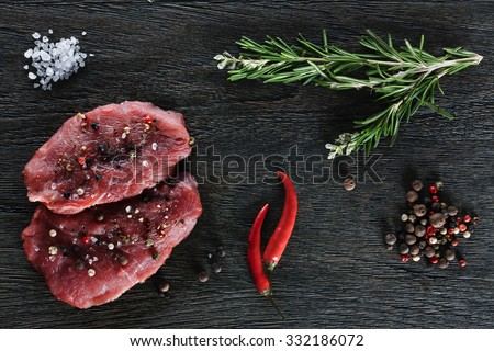Two beef steaks garnished with a couple of rosemary twigs, dwarf chili peppers, sea salt granules and peppercorns on a dark background. Top view. - stock photo