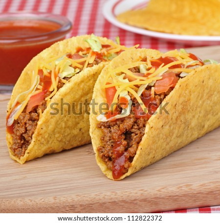 Two beef tacos with lettuce, tomato and sauce - stock photo