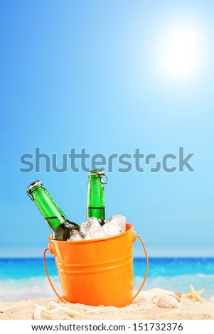 Two beer bottles in a bucket of ice in the sand on a beach - stock photo