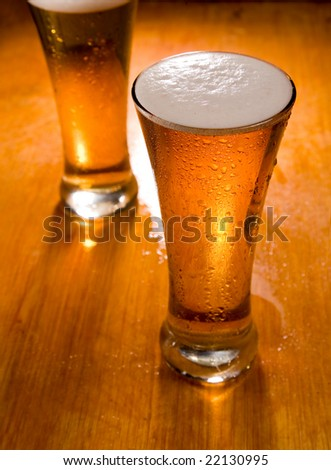 Two beer glasses on wood background, focus on first