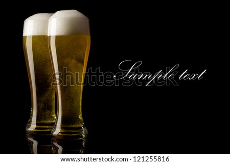 two Beer into glass on a black background - stock photo