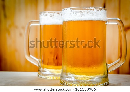 Two beer mugs on the wooden background