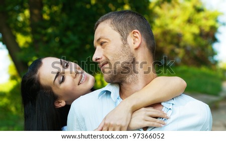 Two beloved against summer green park. Girl has put hands on shoulders of beloved and smiles. - stock photo
