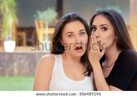 Two Best Friend Girls Whispering a Secret  - Young women sharing gossip and whispering secrets  - stock photo