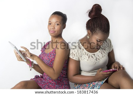 Two best friends usinga tablet and cellphone