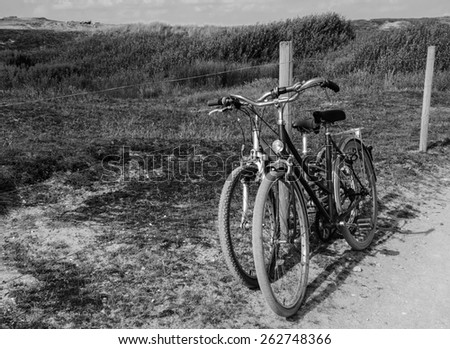 Two bicycles in countryside. Brittany, France. The concept of romance, love and simple everyday life. Aged photo. Black and white.
