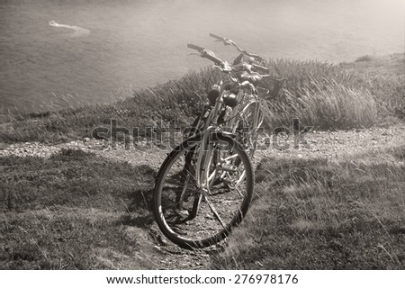 Two bicycles on  hill over the sea in sunny day and a boat sailing at background. Breton coast near Cap de la Chevre. Brittany, France. Sunlight rays. Aged photo. Black and white.