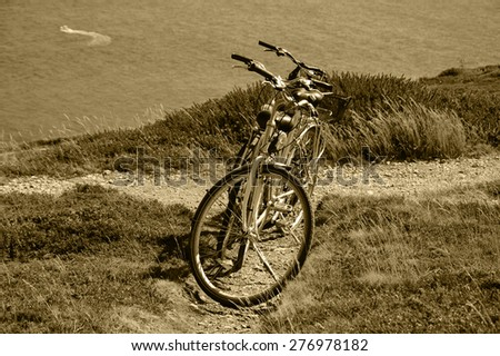 Two bicycles on the hill over the sea in sunny day and a boat sailing at background. Breton coast near Cap de la Chevre. Brittany, France. Active summer vacation background. Aged photo. Sepia. - stock photo