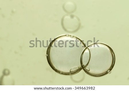 Two big air bubbles flowing over a light green background. - stock photo
