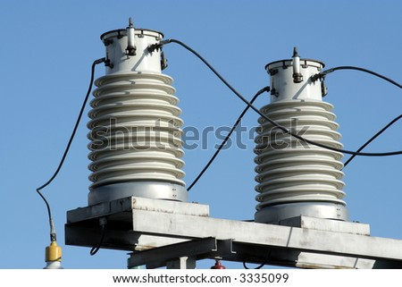 Two big insulators on the high-voltage substation - stock photo