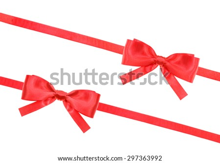 two big red satin bows and two diagonal ribbons isolated on horizontal white background
