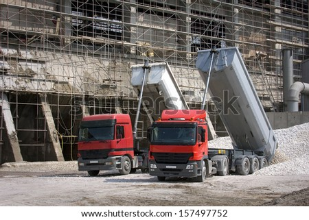 Two big red trucks delivering gravel on construction site - stock photo