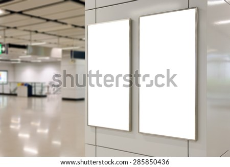 Two big vertical / portrait orientation blank billboard on modern white wall with subway concourse background - stock photo