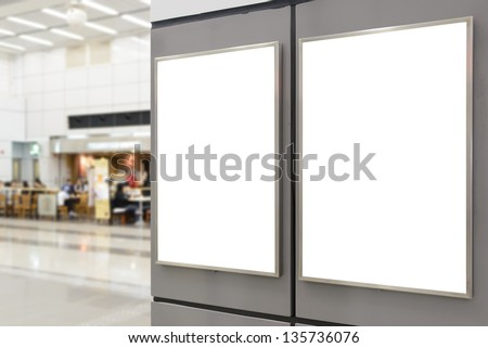 Two big vertical / portrait orientation blank billboard on wall in public open space with blurred cafe background - stock photo