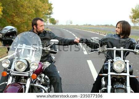 Two bikers on motorcycles handshaking with knuckle on road  - stock photo
