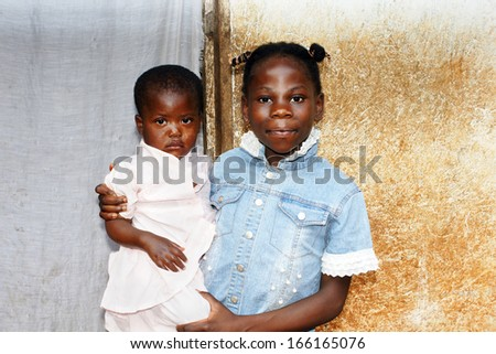 Two black African girls: big or older sister taking care of the family's baby  - stock photo