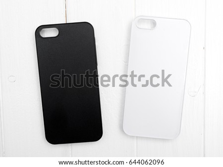 Two black and white iphone cases on white wood, classic iphone design, topview