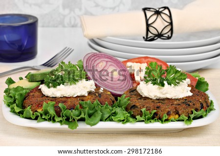 Two black bean vegetarian burgers topped with whipped goat cheese.  Burgers are on a bed of lettuce and garnished with red onion and parsley. - stock photo