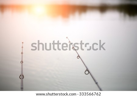 Two black carbon fishing rods with line in natural background of water and sun gleam outdoor hobby recreation summer rest, horizontal picture - stock photo