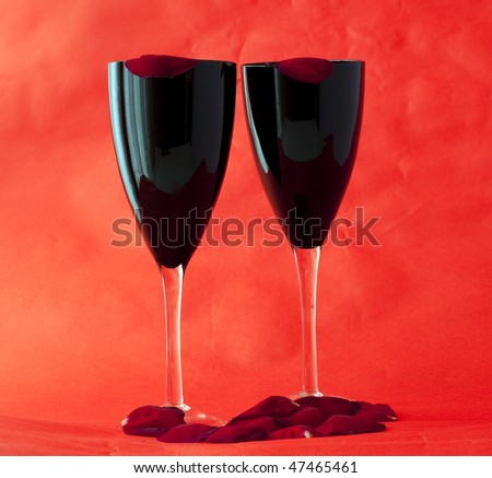 Two black glasses for wine over red background, with petals of rose