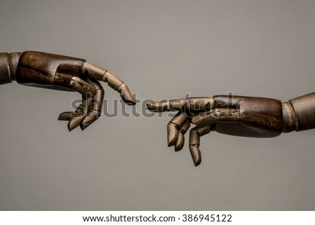 Two black hands mimic the Creation of Adam of Michelangelo. On grey background. - stock photo