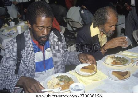 Two black men eating Christmas dinner at homeless shelter, Los Angeles, California - stock photo