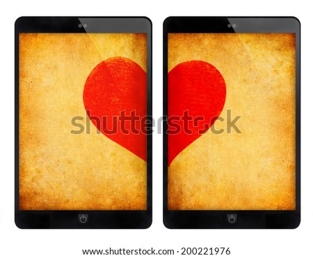 Two black tablet PC same with ipad and red heart on grunge wall, isolated white background. - stock photo