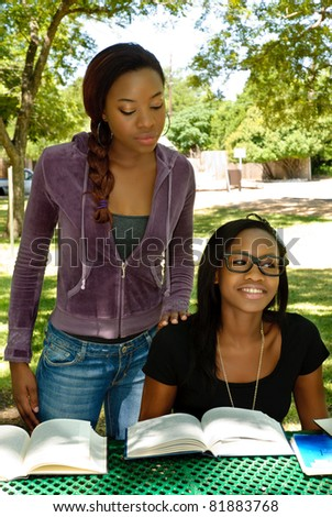 Two black teen study their books at the park, the older girl is helping the younger girl - stock photo