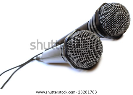 Two black wired karaoke microphones with gray metal grill on isolated background.