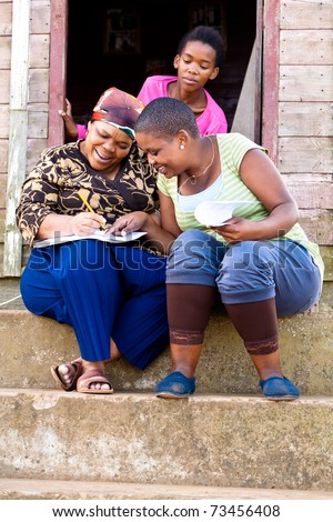 Two black woman filling out a form while sitting on steps and a young black girl stairing over their shoulders. - stock photo