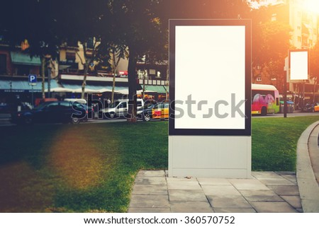 Two blank billboards with copy space for your text message or promotional content, public information boards in urban setting in evening, empty advertising mock up with little banner on background - stock photo