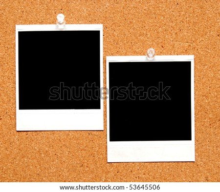 two blank instant film photographs tacked to a bulletin board - stock photo
