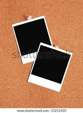two blank instant images pinned to a cork board - stock photo
