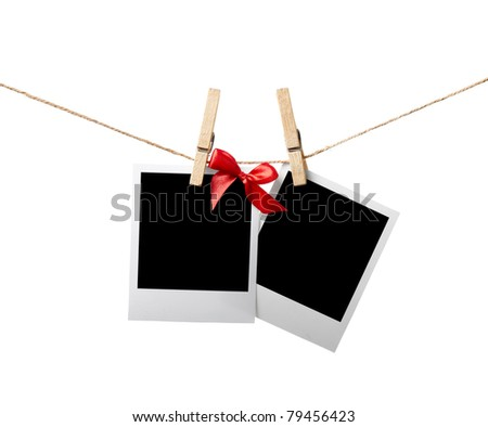Two blank instant photos with red bow hanging on the clothesline. Isolated on white. - stock photo