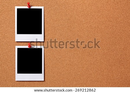 Two blank polaroid photo prints, cork notice board.  Copy space.   - stock photo