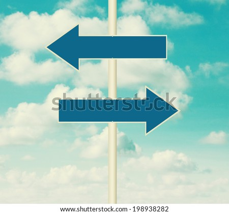 Two blank road signs pointing in opposite directions, blue sky background in vintage style. - stock photo