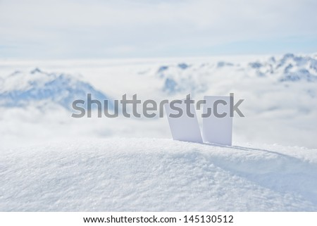 Two blank winter sport ski pass tickets on mountain top. Concept to illustrate winter sport admission fee - stock photo